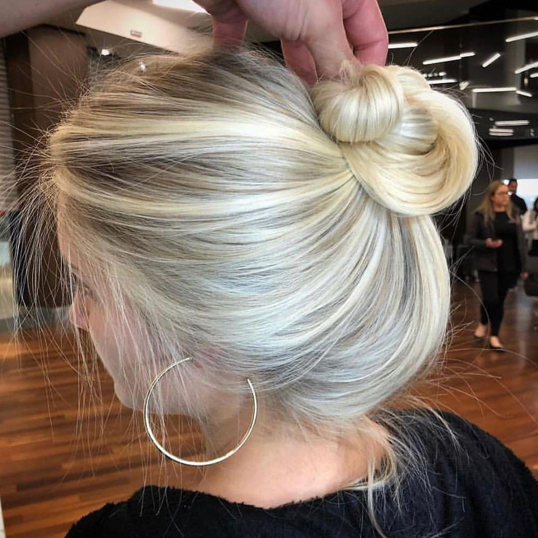 Lunghi capelli biondi con riflessi perlacei e con radici in ombra acconciati con chignon morbido
